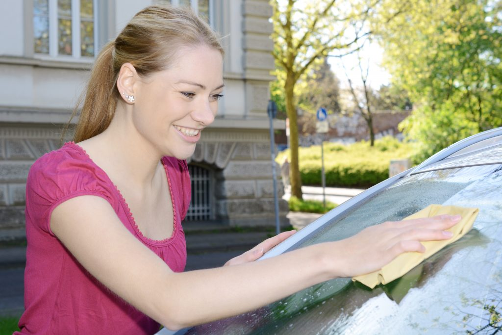 Woman cleaning windscreen